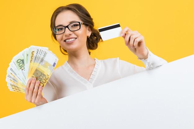 黄色の壁にブランクの看板と彼女の手でお金とクレジットカードを持つ若いビジネス女性の肖像画