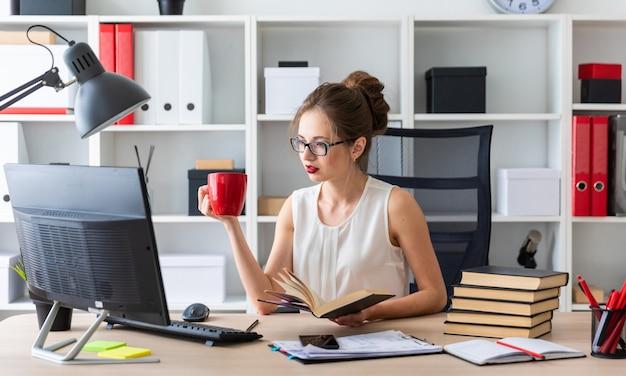 若い女の子がコンピューターテーブルに座って、開いた本と赤いカップを手に持っています。