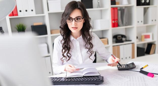 若い女の子がオフィスのコンピューターで働いていて、彼女の手にペンとノートを持っています