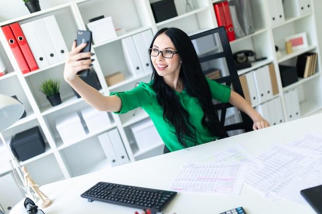 眼鏡をかけた若い女の子がテーブルのオフィスに座って、電話で自分の写真を撮ります。