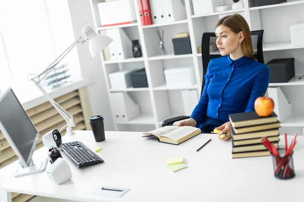 Молодая девушка сидит за компьютерным столом и держит желтый маркер в руке.