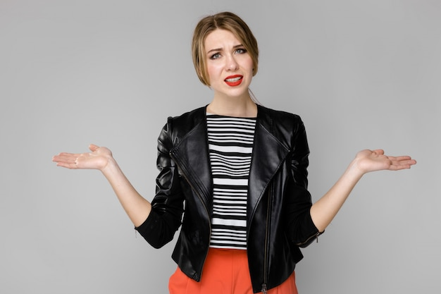 灰色の壁に立っているストライプブラウスと革のジャケットで魅力的な若い困惑したブロンドの女の子