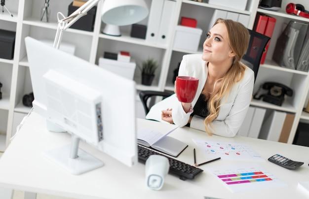 若い女の子がオフィスのコンピューター机に座って、カップを保持しています。