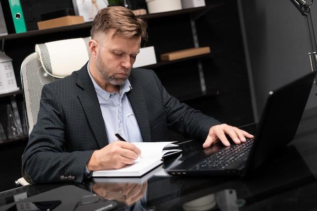 ノートパソコンと日記を扱うビジネス服の若い男