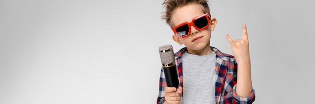 格子縞のシャツ、灰色のシャツ、ジーンズのハンサムな男の子は灰色の壁に立っています。