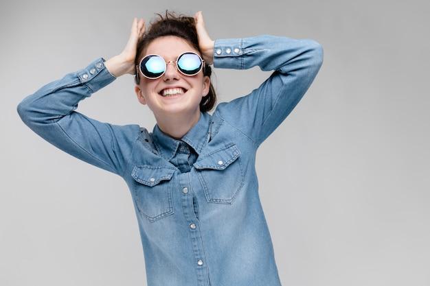 丸いメガネの若いブルネットの少女。