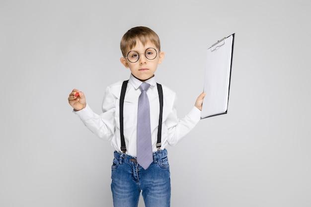 白いシャツ、サスペンダー、ネクタイ、軽いジーンズを着た魅力的な少年が灰色の壁に立っています。