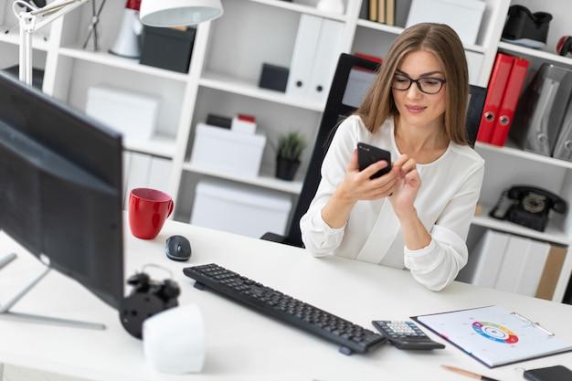 若い女の子がオフィスの机に座って電話を持っています。