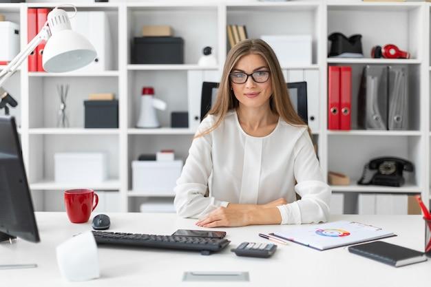 若い女の子がオフィスのコンピューター机に座っています。