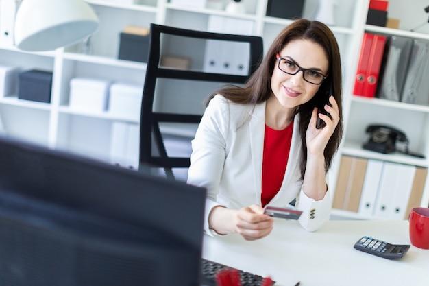 Молодая девушка сидит в офисе за столом и держит банковскую карту и телефон.