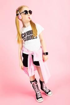 Портрет красивой девушки в шортах, футболке и высоких кедах.