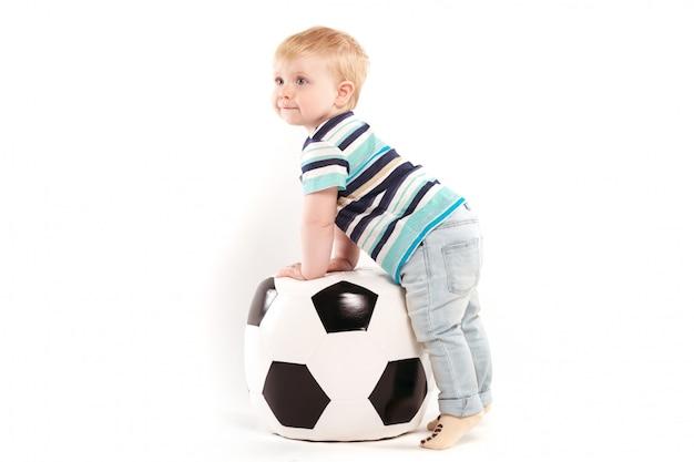 Молодой болельщик с большим футбольным мячом