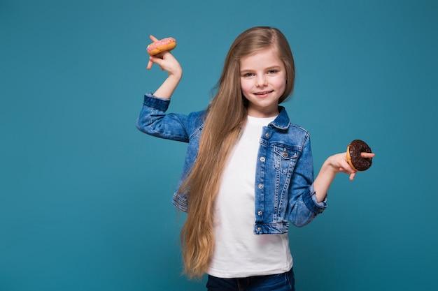 Маленькая симпатичная девушка в джинсовой куртке с длинными каштановыми волосами держит тесто