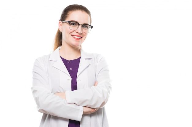 Доктор привлекательных кавказских брюнетка женщина, стоя в офисе, улыбаясь со скрещенными руками
