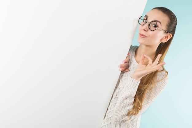 白紙の横断幕を持つ魅力的な若い女性