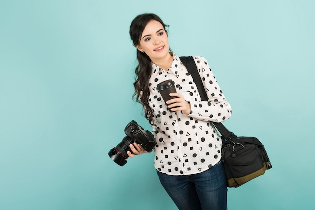 カメラとコーヒーを持つ若い女性