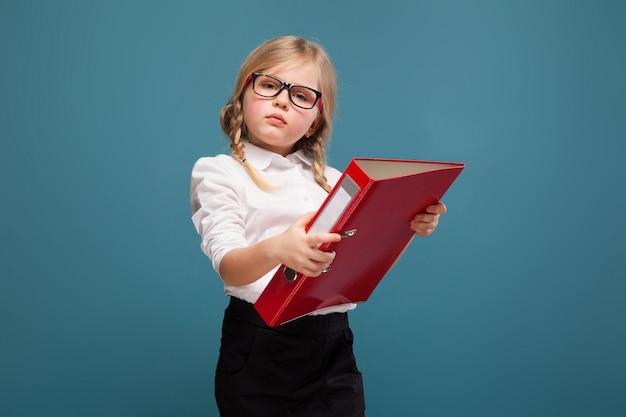 Милая, милая маленькая девочка в белой рубашке, очках и черных брюках держит красную бумажную папку