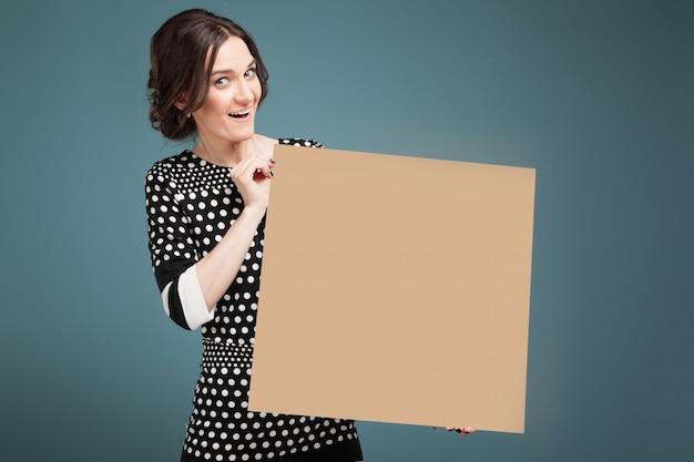 手に大きな紙で立っているまだらの服で格好良い女性の写真