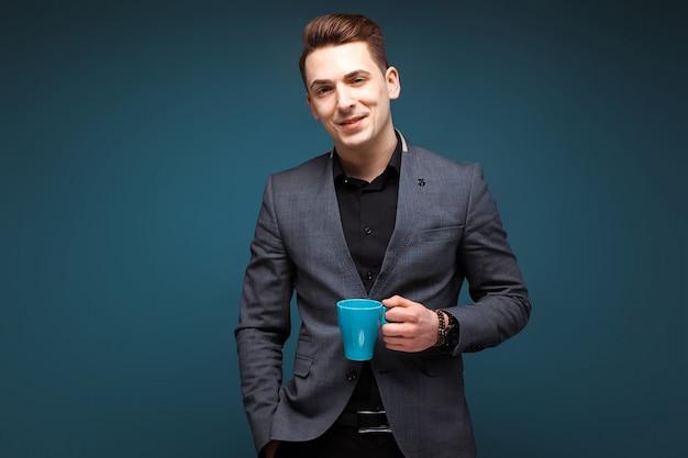 グレーのジャケットと黒のシャツの若い魅力的なビジネスマンが青いカップを保持します。
