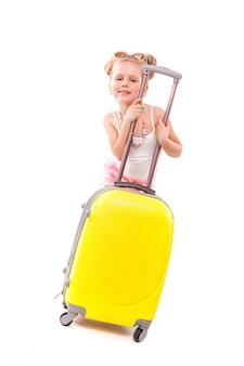 白いシャツ、ピンクのショートパンツ、サングラスでかわいい若い女の子が黄色のスーツケースの近くに立つ