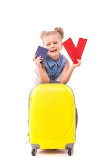 青いシャツ、白いパンツ、サングラスのかわいい女の子が黄色のスーツケースに寄りかかって、赤いカードとパスポートを保持