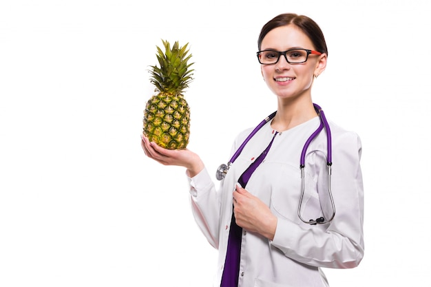 女性栄養士は白に彼女の手でパイナップルを保持します。