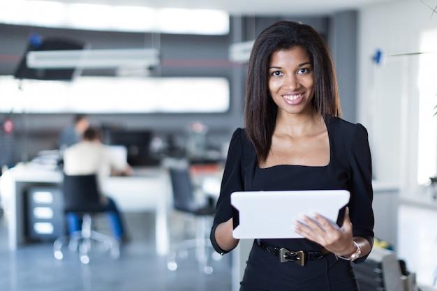 黒の強力なスイートでかなり、若いビジネス女性ホールドタブレット