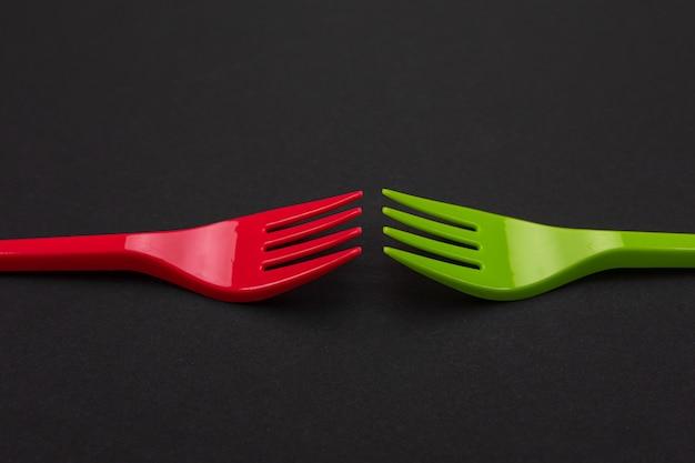背景に分離された使い捨ての赤と緑のプラスチックフォーク