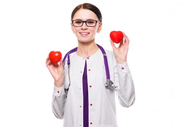 Молодая красивая женщина-врач держит сердца в руках на белом