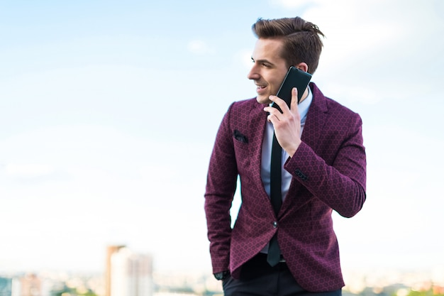赤いスーツとネクタイとシャツの若い真面目な実業家は屋根の上に立ち、電話で話す