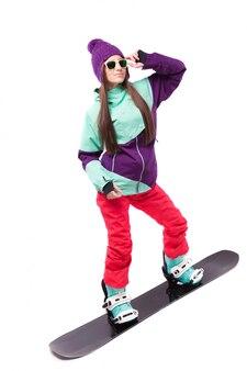 Довольно молодая брюнетка в фиолетовом лыжном костюме едет на черном сноуборде