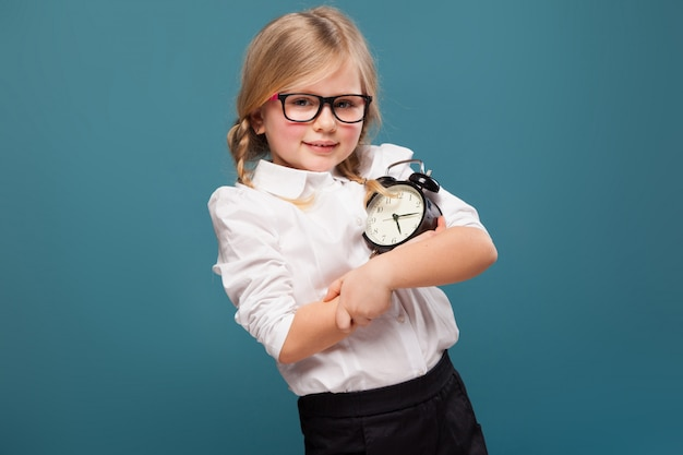 Очаровательная милая маленькая девочка в белой рубашке, очках и черных брюках держит будильник