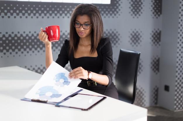 黒の強力なスイートで美しい若いビジネス女性がオフィスのテーブルに座って、赤カップを保持