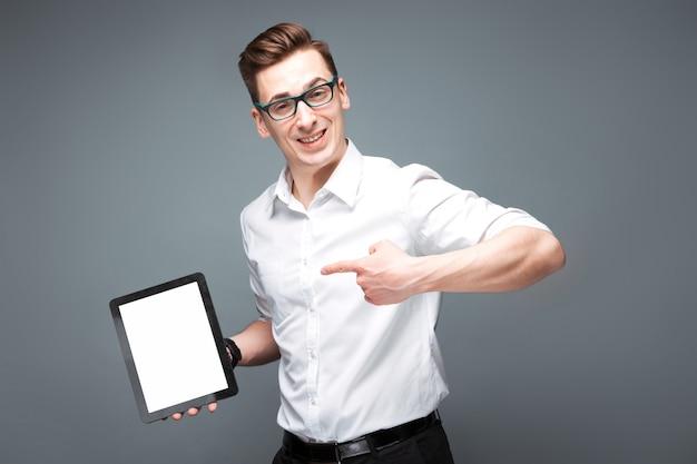 高価な時計、黒眼鏡、白いシャツで成熟した魅力的なビジネスマンが空のタブレットを保持します。
