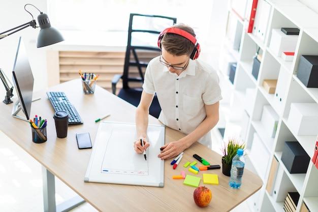 眼鏡とヘッドフォンを持つ若者は、磁気ボードにマーカーを描画します。