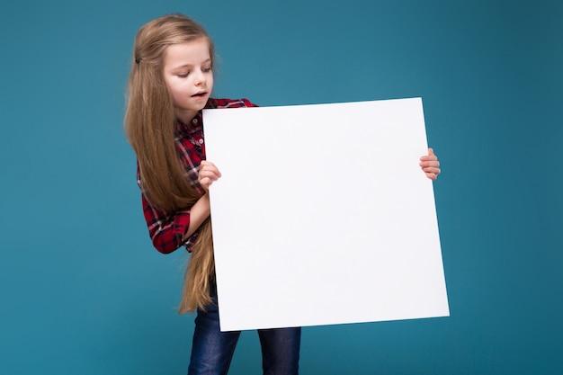長い髪のシャツでかわいい女の子がホワイトペーパーを保持します。