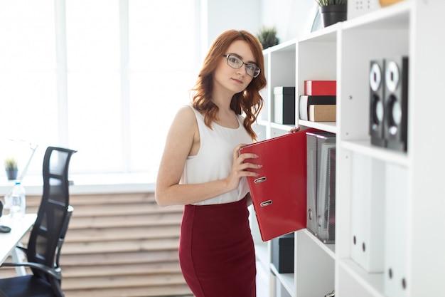 Красивая молодая девушка в офисе тянет папку с документами с полки.