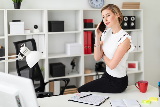 若いブロンドの女の子がオフィスの机に座って電話で話しています。
