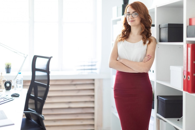 Красивая молодая девушка стоит в офисе возле полки с документами.