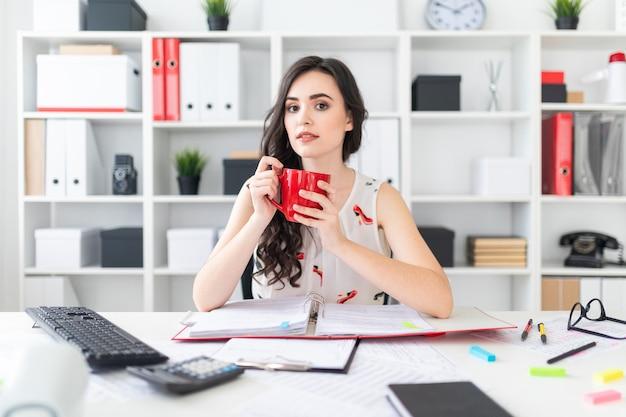美しい少女はオフィスの机に座って、手に赤いマグカップを保持しています。