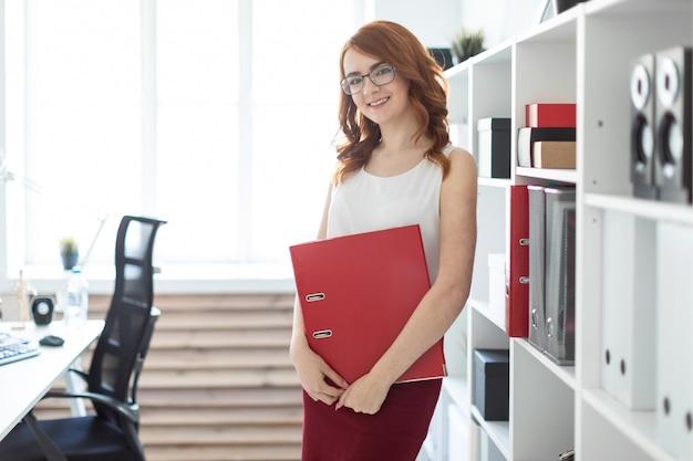 美しい少女がオフィスのスタックの近くに立って、手に書類の入ったフォルダーを持っています。
