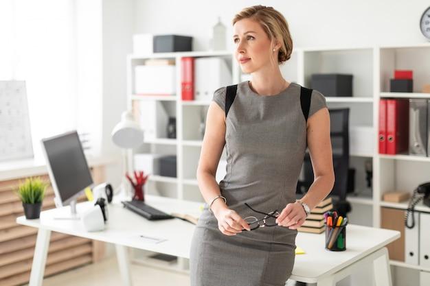 Молодая девушка стоит возле стола в офисе и держит очки в руке.