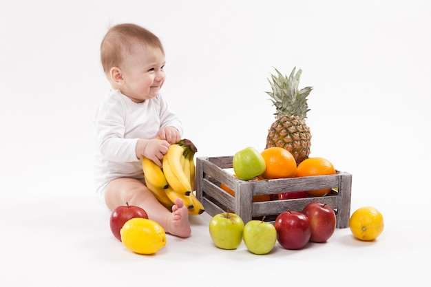 Глядя на фрукты мило улыбающегося ребенка на белом среди фруктов