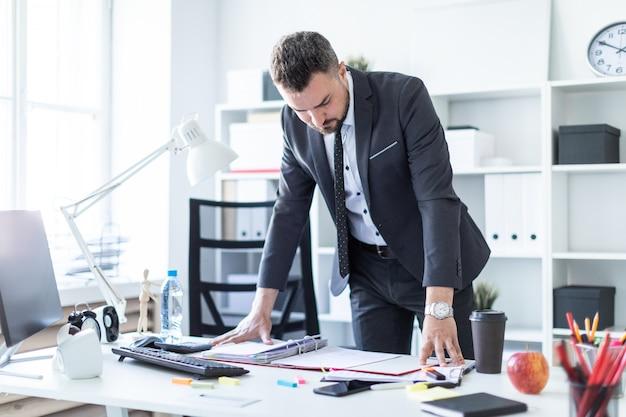 男は事務所に立ち、手をテーブルに置き、文書を見る。
