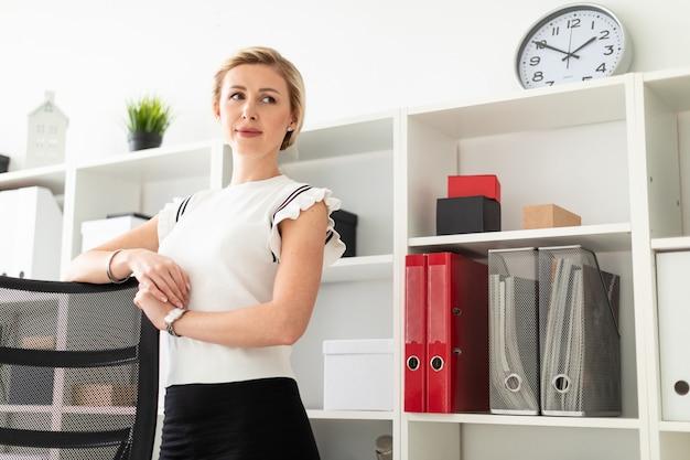 若いブロンドの女の子が、書類のある棚の隣のオフィスに立ち、両手を椅子の後ろに置いています。