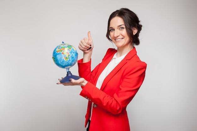 手で地球球と赤いブレザーのきれいな女性の写真