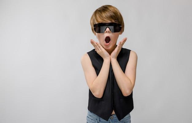 灰色の顔の近くに彼の手を繋いでいるスタジオに立っているサングラスで愛らしい驚いた少年の肖像画