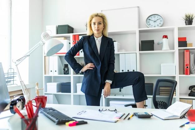 若い女の子がオフィスのテーブルの近くに立ち、足を椅子に置きます。