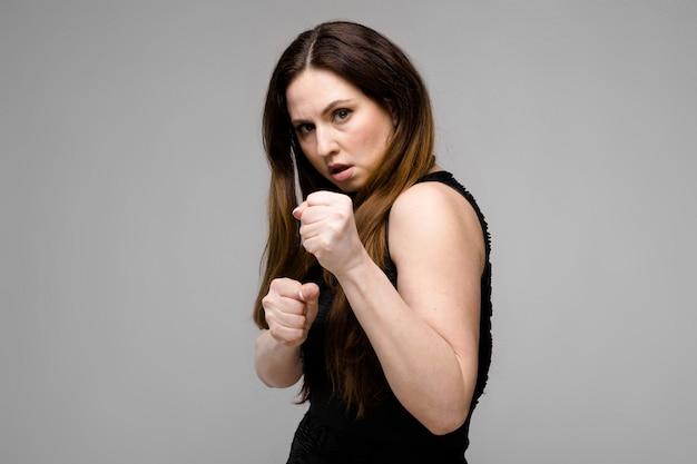 Эмоциональная довольно уверенная серьезность плюс модель размера стоя в боксе студии на сером
