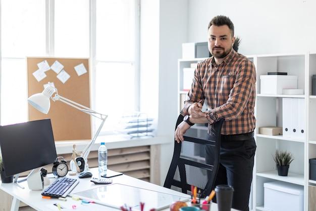 男がコンピューターデスクの近くのオフィスに立ち、椅子の後ろに手を置きます。